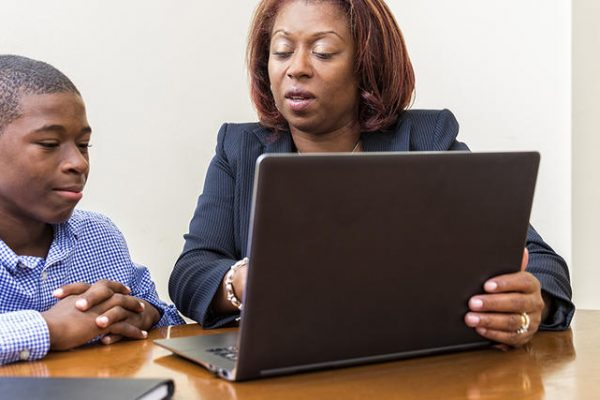 A school teacher reviews reports with her student on her laptop.