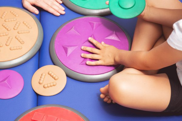 Child with occupational therapist touching sensory integration equipment